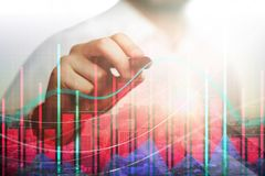 Trade and analysis concept. Male hand drawing creative bright forex chart on city background with sunlight. Trade and analysis concept. Double exposure Royalty Free Stock Image