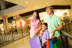 In trade center. Portrait of pretty female showing something to her husband and son during shopping Royalty Free Stock Photography
