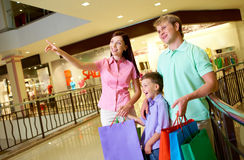 In trade center. Portrait of pretty female showing something to her husband and son during shopping Stock Photography