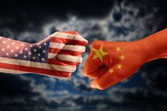 Trade conflict, fists with the flags of USA and China against ea. Ch other, dramatic sky with clouds in the background Stock Images