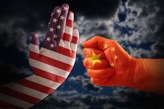 Trade conflict, USA flag on a stop hand and China flag on a fist. Against a dramatic cloudy sky royalty free stock photography