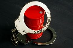 Trade embargo and sanctions. Barrel of oil and handcuffs. Trade embargo and sanctions concept. Barrel of oil and handcuffs stock photos