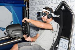 A trade fair visitor is playing a racing game with vr headeset Stock Photo