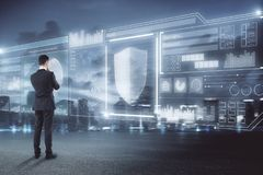 Trade, finance and safety concept. Businessman looking at abstract digital business interface on blurry night city background. Trade, finance and safety concept royalty free stock photo