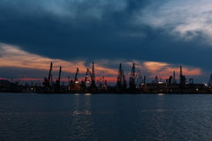 Trade harbor in night time. Trade harbor with port cranes in the sunset Royalty Free Stock Photo