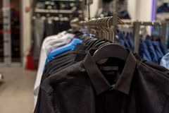 Black, blue and white men`s shirts on hangers inside the store, close-up with a blurred background stock images
