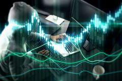 Trade and malware concept. E view of hacker using laptop at blurry desktop with coffee cup and glowing forex chart. Trade and malware concept. Double exposure stock photo