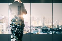 Trade and research concept. Back view of thoughtful young businessman standing in modern business interior with Bangkok city view. Trade and research concept stock images