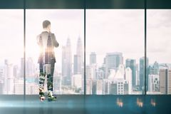 Trade and research concept. Back view of thoughtful young businessman standing in modern business interior with Kuala Lumpur city view. Trade and research royalty free stock image