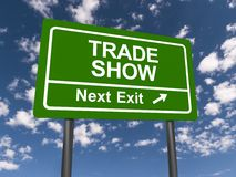 Trade show next exit. Green highway sign with white block text for trade show next exit with directional arrow on blue sky with white clouds royalty free stock photography