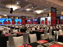 Trade Show. Room with no people many tables and chairs in great hall. Tables have black tablecloth and chairs are white royalty free stock images