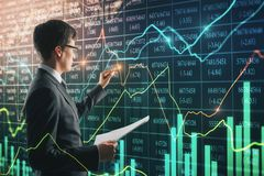 Trade and stock concept. Side view of attractive young european businessman using forex chart interace on blurry background. Trade and stock concept. Double stock photos