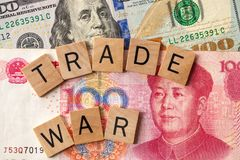 Trade war between USA and China concept/ Tariff law. Trade war written over 100 USA dollar and 100 Chinese yuan banknotes Stock Photos