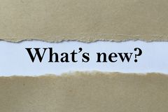 What's new ?. Text 'What's new ?' in black script on pale blue paper  viewed through a slit (gap) in fawn card  with torn edges for emphasis stock photo