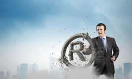 Trademark. Angry businessman crashing stone trademark with karate punch royalty free stock image