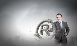 Trademark. Angry businessman crashing stone trademark with karate punch stock image