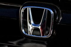 The trademark symbol of Honda in the frontside of a black car - photography. Close-up view on the trademark symbol of Honda, in the front side of a black car stock photos