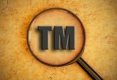 Trademark symbol. Magnifying glass focusing on trademark sign Stock Image