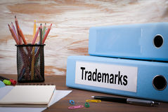 Trademarks, Office Binder on Wooden Desk. On the table colored pencils, pen, notebook paper Royalty Free Stock Photos