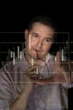 Trader analyze stock. Young man in pink shirt as a trader measures fingers candle stick graph to analyze stock over black background royalty free stock image