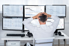 Trader with hands on head looking at graphs on screens Stock Image