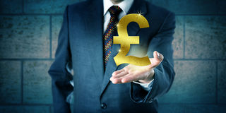 Trader Holding A Golden British Pound Sterling Symbol. Forex trader holding a golden British Pound Sterling symbol in the open palm of his left hand. Business royalty free stock photo