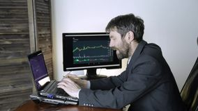 Trader working on laptop on crypto stock exchange. businessman keep track of exchange currency exchange chart at the stock footage