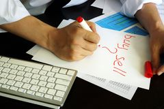 Trader is writing buy or sell in a note. Trader is writing buy or sell in a note in an office Royalty Free Stock Photo