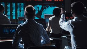 Traders analyzing data on exchange. Financial traders working in modern office analyzing statistics and driving trade on exchange Royalty Free Stock Photo