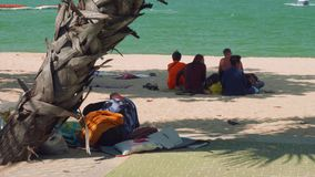 Traders sit in shadow of trees escaping heat and having lunch stock video footage