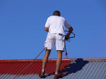 Tradesman. A spray painter restoring the roof of a house Royalty Free Stock Photography