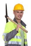 Tradesman carrying a pickaxe. Tradesman in neon jacket carrying a pickaxe royalty free stock photos