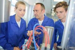 Tradesman explaining machinery to apprentices Royalty Free Stock Photo
