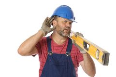 Hearing Loss for a Worker. A tradesman with his hand to his ear, a concern for noisy work sites and the health of personnel stock photo