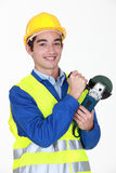 Tradesman holding an angle grinder Stock Photography