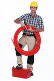 Tradesman holding corrugated tubing Stock Photo