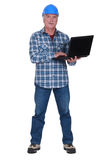 Tradesman holding a laptop Stock Images
