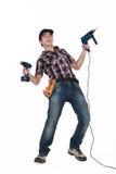 Tradesman holding power tools. A tradesman holding his power tools stock photo