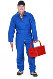 Tradesman holding a toolbox. Tradesman holding a tool and his toolbox Stock Photo
