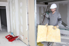 Tradesman installing insulation Stock Images