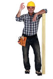 Tradesman leaning on planks of wood Stock Photo