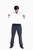 Tradesman looking at blank sign in his hands Royalty Free Stock Photos