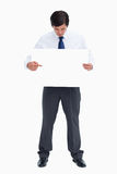 Tradesman pointing at blank sign in his hand. Against a white background Stock Photos