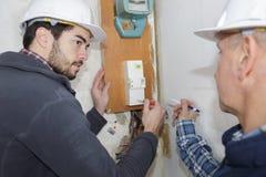 Tradesman repairing distribution board stock image