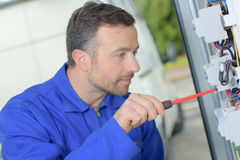 Tradesman repairing distribution board. Tradesman repairing a distribution board stock photography