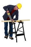 Tradesman sawing a plank Royalty Free Stock Images