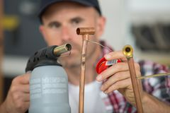 Tradesman soldering with blow torch. Man Royalty Free Stock Photo