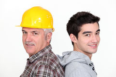 Tradesman standing back to back. With his apprentice royalty free stock photos