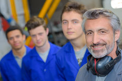 Tradesman with three apprentices Royalty Free Stock Image