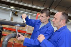 Tradesman training two apprentices royalty free stock photo